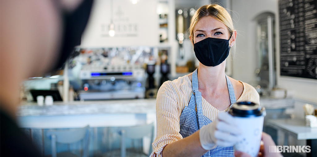 A masked retail employee serves customers with social distancing measures in place.